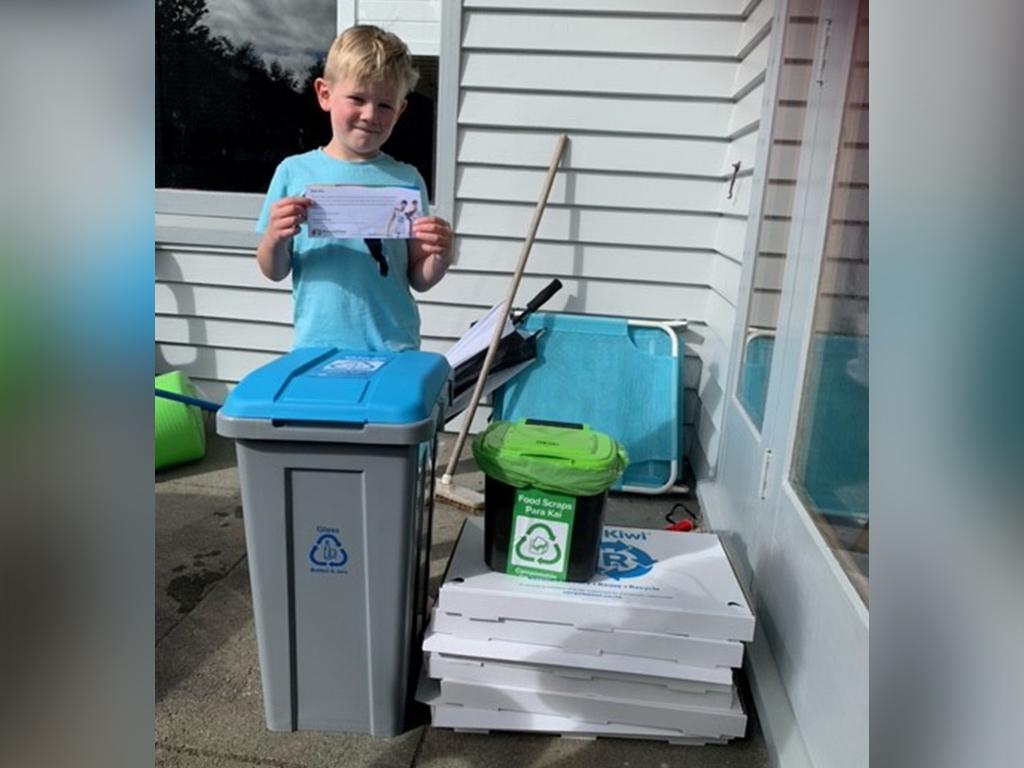 Boy with recycling bins.