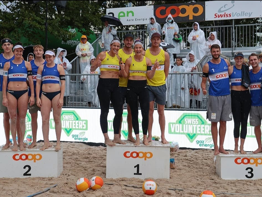 Beach volleyballers standing on winners' podiums.